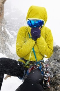 Mid adult woman wearing yellow jacket and ski goggles in snow